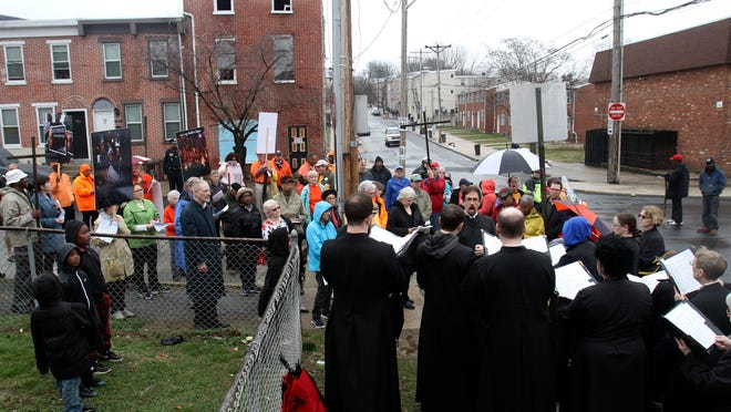 Participants in a Good Friday urban stations of the cross procession listen as the choir of the Episcopal Church of Saints Andrew and Matthew sing a spiritual at the corner of W. Fifth and N. Monroe Streets in Wilmington. The procession looped through the west center city neighborhood with stops at street corners where violence has occurred.