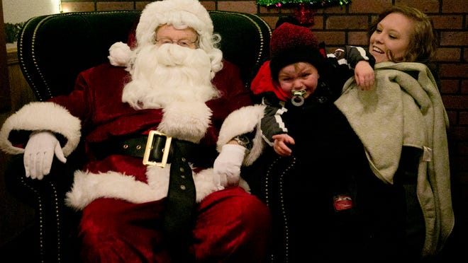 Lindsey Maurer of Adams, right, holds her son Leigham Maurer, 2, as they take their photo with Santa at Rotary Winter Wonderland in Marshfield.