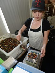 Shelby Banik weighs out a serving for their deliverable meals at Healthy Chef Meals on Olive Street.