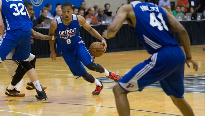 Detroit Pistons guard Spencer Dinwiddie, left, dribbles through the Miami Heat during the NBA summer league in Orlando on July 6, 2015.