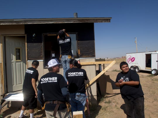 Navajo YouthBuilders students work on a home renovation project Thursday in Shiprock.