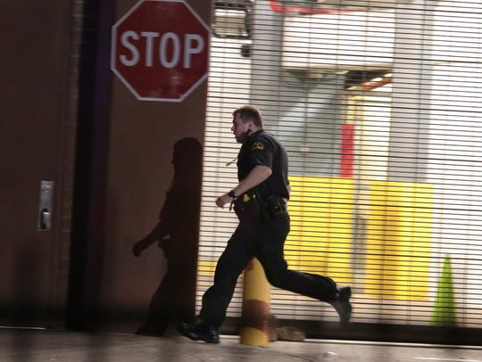 A Dallas police officer runs past a gated garage entrance