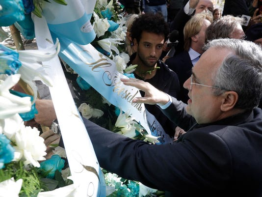 Lazio soccer team president Claudio Lotito, accompanied by Lazio player Felipe Anderson, center, places a wreath outside Rome's Synagogue, Tuesday, Oct. 24, 2017. Lazio fans have a long history of racism and anti-Semitism and the Roman club's supporters established another low over the weekend when they littered the Stadio Olimpico with superimposed images of Anne Frank _ the young diarist who died in the Holocaust _ wearing a jersey of city rival Roma. (AP Photo/Gregorio Borgia)