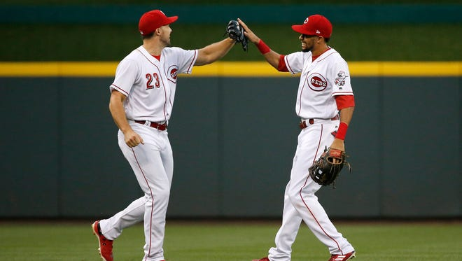 Cincinnati Reds left fielder Adam Duvall (23) and center fielder Billy Hamilton (6) high five in the outfield after Duvall's play in left field in the top of the fifth inning of the MLB National League game between the Cincinnati Reds and the San Diego Padres at Great American Ball Park in downtown Cincinnati on Tuesday, Aug. 8, 2017. The Reds fell 7-3 in game two of the four game series.
