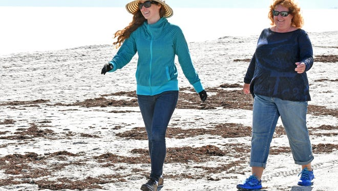 """Chelsea Kenyon and her mother, Heather Kenyon are visiting from Canada, and found  weather suitable for a walk on the beach. """"It feels amazing, because it's way warmer than Canada"""", said Chelsea. Very few beachgoers were out on Tuesday along Cocoa Beach during chilly weather."""