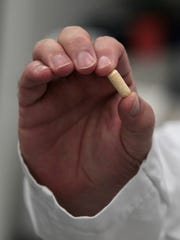 Eric O'Brien, production manager, holds up a single finished capsule of probiotic.
