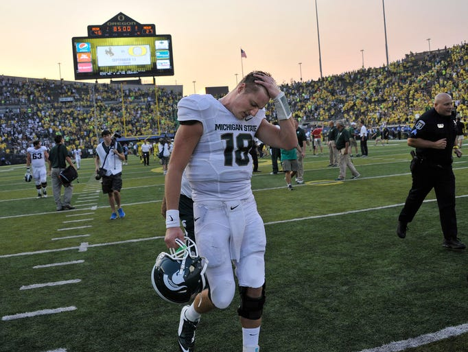 MSU quarterback Connor Cook rubs his head and trudges off the field as MSU falls to Oregon 46-27, at Autzen Stadium in Eugene, OR on Saturday. The Spartans lead the Ducks by nine points in the third quarter but couldn't hang-on.