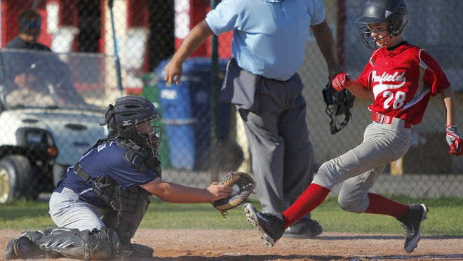 Greece Little League catcher Ryan Coughlin, left, tags out Penfield's Noah Sobko at home in the first inning of the 2014 District 4 Little League Championship on July 10, 2014.