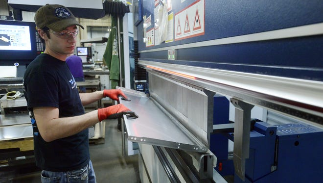 Todd Moulton bends an aluminum panel last month on a computerized press brake. It will be used in a truck bed cover at Westland Manufacturing in Sioux Fall s. Todd Moulton bends an aluminum panel on a computerized press brake that will be used in a truck bed cover Wednesday at Westland Manufacturing in Sioux Falls, April 23, 2014.