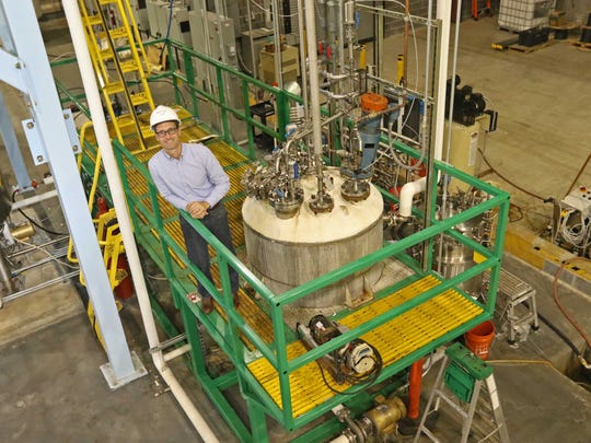 Bryan Tracy, CEO and chief technology officer of White Dog Labs, stands next to a biological reactor in the company's pilot and demonstration facility near New Castle.
