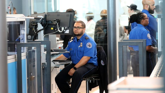 An employee (L) of the Transportation Security Administration