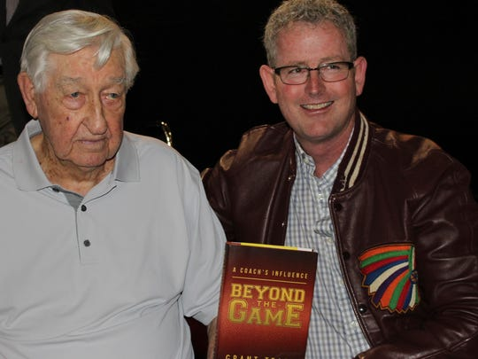Hershel KImbrell, left, and former McMurry University basketball player Stan Laing posed with a book signed by former McMurry and Baylor coach Grant Teaff. Laing, who wore his letter jacket at the event, stopped in Waco on the way to pick up the book from Teaff, who was hospitalized.
