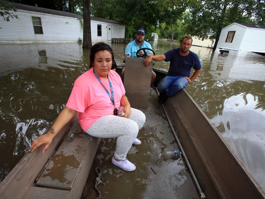 Jasmine Fontenot (front) gets a boat ride to her home with the help of Darius Girouard (back) and Fabian LeBlanc (right) after her family was evacuated do to high water from recent rain Tuesday, Aug. 16, 2016, in Abbeville, Louisiana.