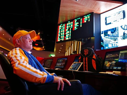 Amado Nanalang watches basketball games while making bets at a sports book owned and operated by CG Technology in Las Vegas.