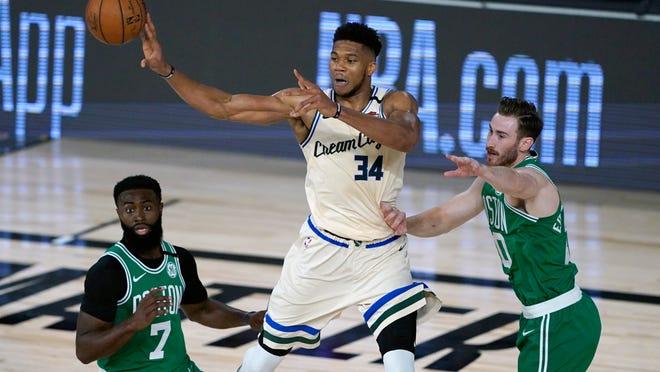 The Bucks' Giannis Antetokounmpo (34) passes around the Celtics' Jaylen Brown (7) and Gordon Hayward during the first half Friday night.
