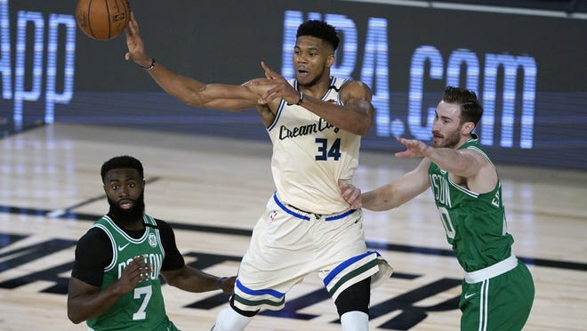 Giannis Antetokounmpo (middle) and the Milwaukee Bucks were beneficiaries of some questionable non-calls down the stretch in the Bucks 119-112 win over the Celtics Friday night.