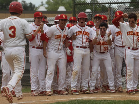 Bergen Catholic greets David LaManna at home plate after he hit his solo home run in the fourth inning. It was the only run of the game and was the winning hit for the Crusaders.