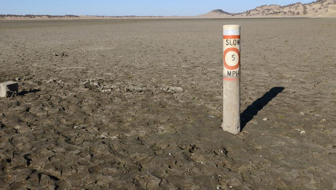 A 5-mph boating speed limit buoy is stuck in the ground at the site of Calif.'s Black Butte Lake, where drought has done away with the water.