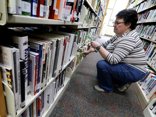In this Journal Sentinel file photo, Library Specialist Colleen Yaggie pulls books from the Germantown Community Library stacks to be held for patrons or to be transferred to one of 33 other libraries in the four-county Monarch Library System.