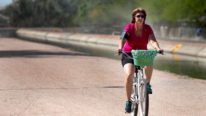 Wendy Baker rides on the Paseo Trail, a multiuse path that runs along the canal in Chandler. The southeast Valley has 34 miles of paved paths along the canal system.