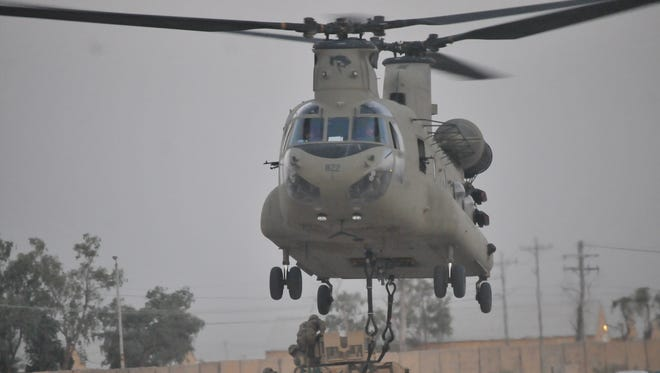 A hook-up team, consisting of soldiers with 1st Battalion, 502nd Infantry Regiment, Task Force Strike, attach an M1151 Humvee to a CH-47 Chinook helicopter during a sling load training exercise July 16 2016, in Taji, Iraq.