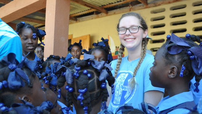 Merrol Hyde Magnet School senior Jordan Wales is surrounded by students from St. Bertin in Haiti, where she delivered 400 books for a mobile library.