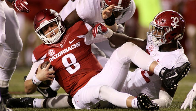 Arkansas' Austin Allen (8) is pulled to the ground by Alabama's Rashaan Evan (32) during the third quarter of an NCAA college football game Saturday, Oct. 8, 2016, in Fayetteville, Ark. Alabama won 49-30.