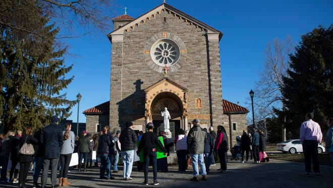 Padua Academy parents, students, and community members stand together in protest of the removal of Padua Academy Head of School Cindy Mann outside of St. Anthony of Padua Church before  9 a.m. Mass on Sunday.