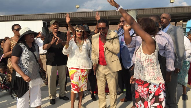 Evangelist Bonita Shelby with her husband, Pastor Don Shelby of Burning Bush International Ministries, as he prays over the unveiling of a Baphomet monument on July 25, 2015, on the sidewalk across the street from Bert's Marketplace in Eastern Market in Detroit.