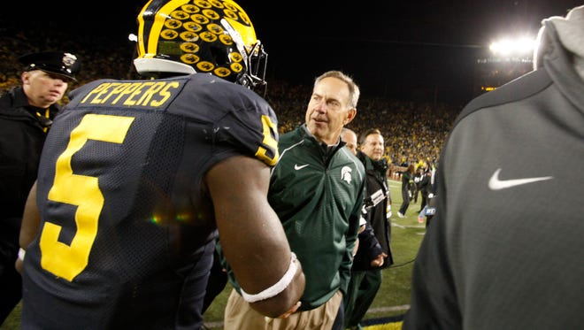 Michigan State coach Mark Dantonio  shakes hands with Michigan's Jabrill Peppers after Michigan State defeated Michigan 27-23 in the last 10 seconds of the game on a Jalen Watts-Jackson  winning touchdown that he picked up on a  muff punt , Saturday, Oct. 17, 2015. in Ann Arbor.