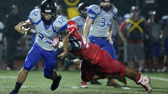 Central High School's Marlon Tuipulotu (51) tackles Woodburn's Ivan Soto during their game on Friday, Oct. 30, 2015, in Independence, Ore.