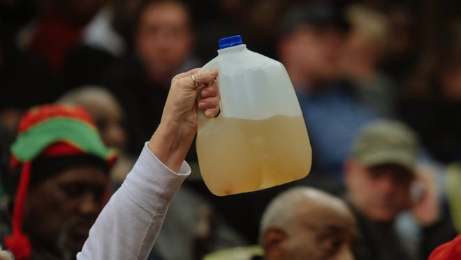 Flint resident Gladyes Williamson-Bunnell holds a sample of water that came from her home she saved from August 2014.