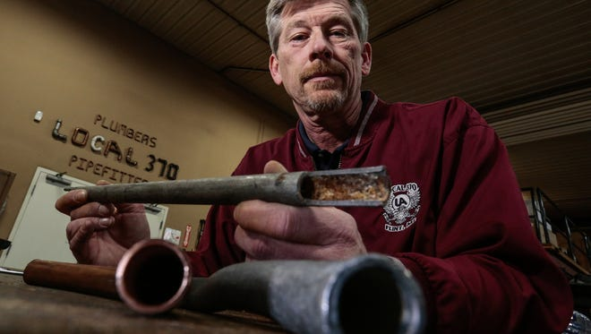 Plumbers & Pipefitters U.A. Local 370 Business Manager Harold T. Harrington holds a corroded galvanized pipe from his house in Flint that is 80 years old.