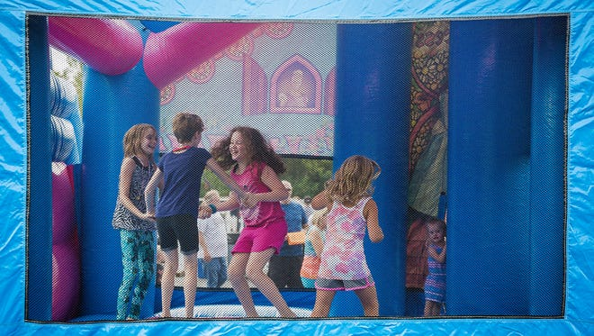 Children play in a bounce house during Fam Fest Saturday morning.