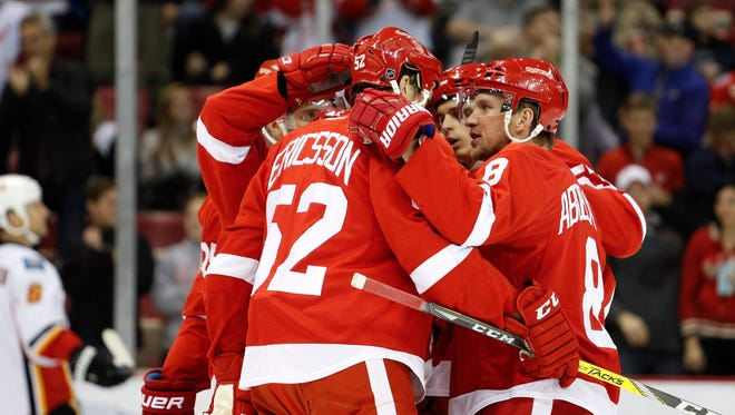 Red Wings left wing Tomas Tatar (21) celebrates with teammates after scoring a goal against the Flames during the first period Sunday at Joe Louis Arena.
