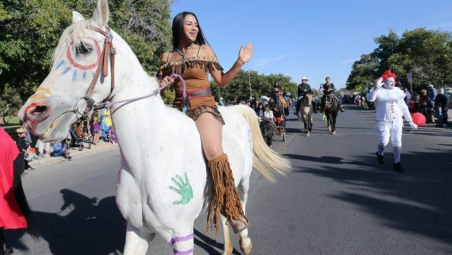 Jessica Dixon rides along the KLAQ Halloween Parade route dressed as Pocahontas Tuesday.