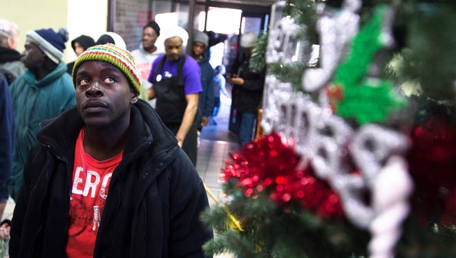 Michael Parker looks at the christmas tree as he waits in line for dinner at the Salvation Army in Montgomery, Ala., on Wednesday, Jan. 3, 2018.