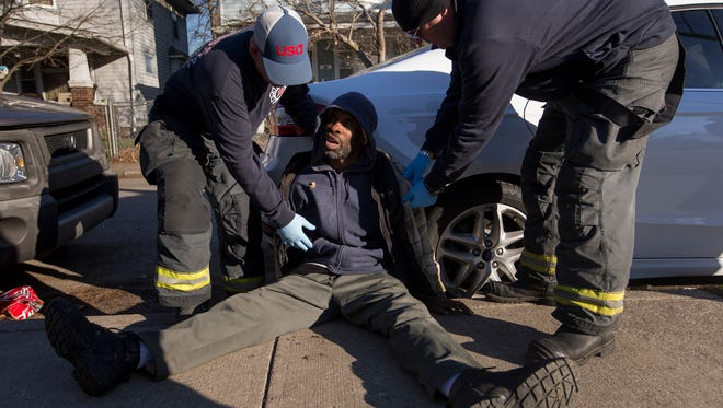 A man, suspected on being on the street drug KD, is tended to by Engine 27 personnel, Indianapolis, Friday, Dec. 1, 2017. He was transported to a local hospital by paramedics.