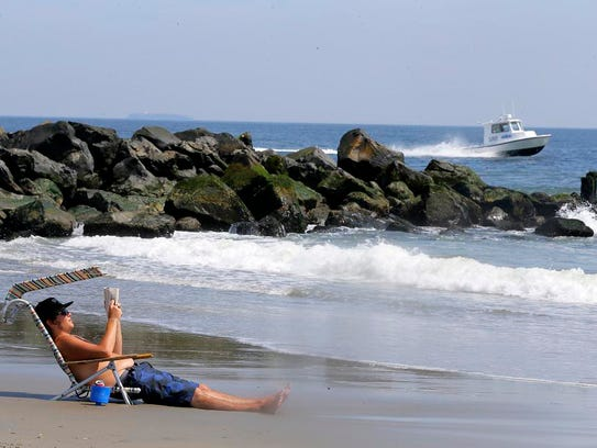 John E. Kinasczuk of Long Branch reads on the beach