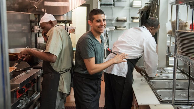 """Ebram Said walks past cooks Muhamad Ali """"Abu Rasheed,"""" left, and Mubarak Muhammad in the kitchen of Aldeerah Saudi Arabian restaurant in Vienna, Virginia on June 29, 2016. Said helps his Muslim coworkers by working extra hours and taste-testing dishes throughout the Muslim holy month of Ramadan, when observant Muslims fast from food and drink during the day."""