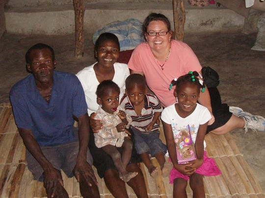 De Pere resident Michelle Good, back right, sits on the floor with the Louis family in their desolate home on Good's visit to the Republic of Haiti last year. Good and her husband Ryan are sponsors of Ghislande, front right, the oldest of the Louis family's three children.