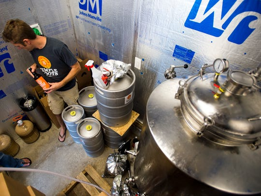 Dan Ukolowicz pulls a bottle of a new autumn saison from the cooler. The new brew will be released at the Burlington Farmers Market Saturday.