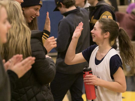 Hartland Unified's Jaimie Flores, right, receives a high-five from Hartland varsity basketball player Emily Messner during a basketball game partnering special education students and their peers Thursday, Jan. 25, 2018.