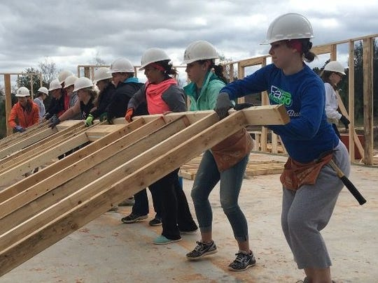 Volunteers with Habitat for Humanity help build a home