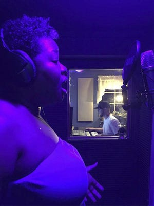 This undated image shows Rashida Bryant singing at a home recording studio in Long Island, N.Y. Bryant, 44, is an Atlanta-based voice instructor through Wyzant,  an online marketplace for private tutors, who saw her client roster double from April to June, when she had 30 students. Her students range in age from early teenagers to people in their late 60s.