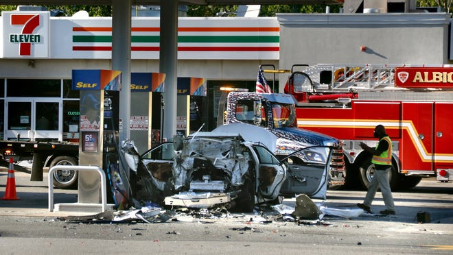 Workers sweep up debris after an explosion at a Sunoco station on Route 116 in Lincoln on Tuesday afternoon. A leaking tank of fuel for a plumber's cutting tool was apparently ignited when the driver unlocked the back with the key fob.