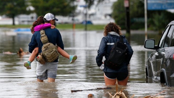 Don Noel carries his daughter Alexis, 8, with his wife Lauren, right as they walk through a flooded roadway to check on their boat in the West End section of New Orleans,  June 21, 2017 as Tropical Storm Cindy headed ashore.