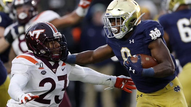 Notre Dame running back Jafar Armstrong (8) stiff arms Virginia Tech linebacker Rayshard Ashby (23) during the second half of an NCAA college football game, Saturday, Nov. 2, 2019, in South Bend, Ind.