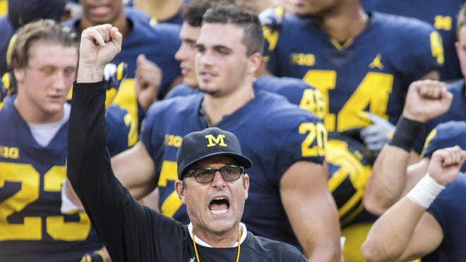"""Michigan head coach Jim Harbaugh leads his players and fans in singing """"Hail to the Victors"""" after a preseason open practice session by the NCAA college football team at Michigan Stadium in Ann Arbor, Mich., Sunday, Aug. 26, 2018."""