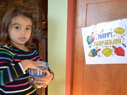 Two-year-old Vera Corona plays with a menorah snow globe in her Catawba home. Vera's mother is Jewish, and her father is Catholic, so she and her brother celebrate both Hanukkah and Christmas each year.